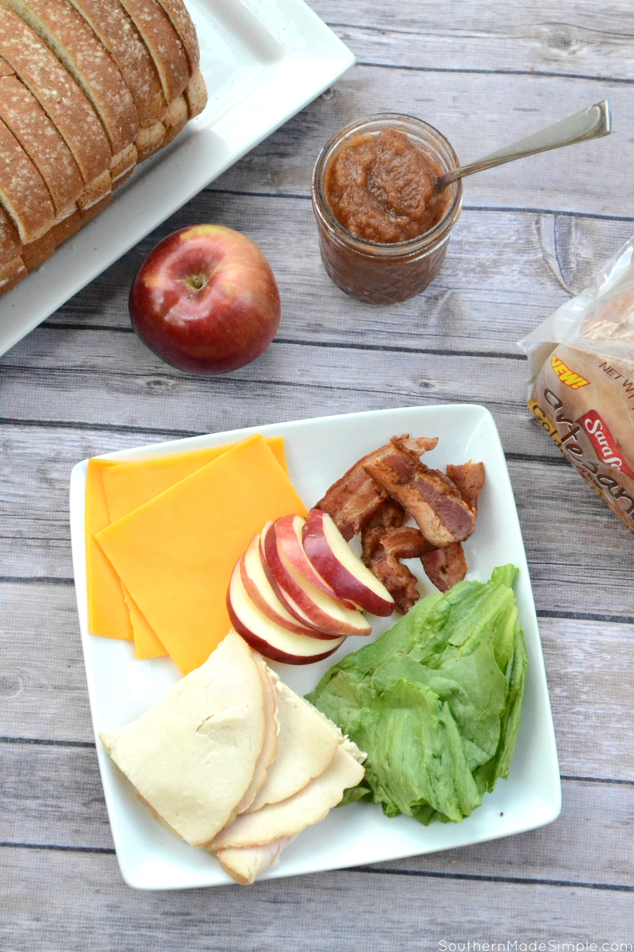 Forget what you know about turkey sandwiches. This Carved Turkey, Cheddar and Apple Butter Club Sandwich is stacked high with fresh apple slices, crispy bacon, thick carved turkey breast and the sweetest apple butter your mouth has ever tasted, and it's all nestled between three slices of Sara Lee Artesano Golden Wheat Bread! #ArtesanoGoldenWheat #Ad