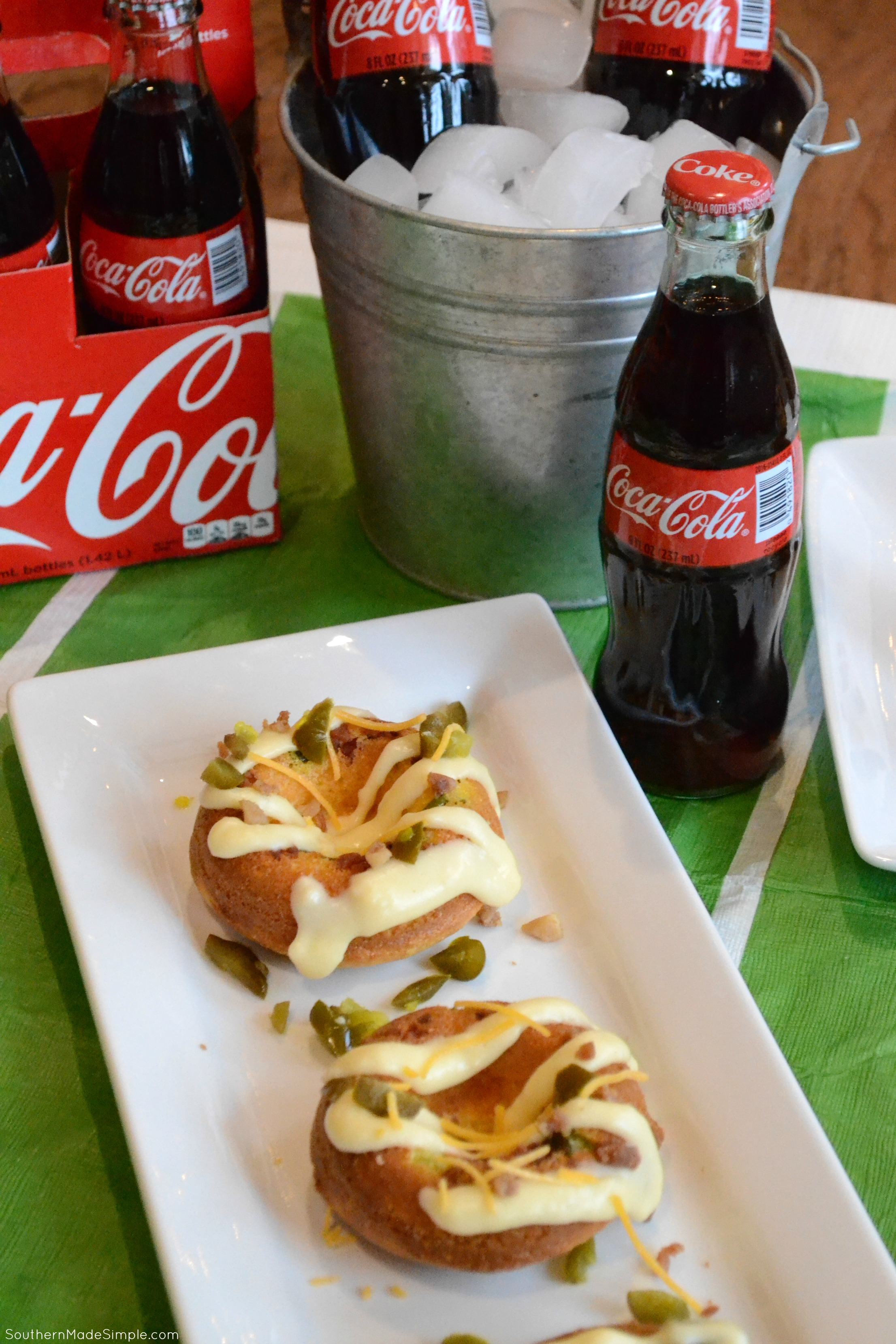 Serve up some spicy goodness during the big game with these savory Cheddar Bacon Jalapeno Doughnuts! They're a cheesy cornbread base with a spicy jalapeno cheese sauce that is in a league of it's own! Pair it with an ice cold Coca-Cola and you've got a winning hand! #ServeWithACoke #BowlGames #CollectiveBias