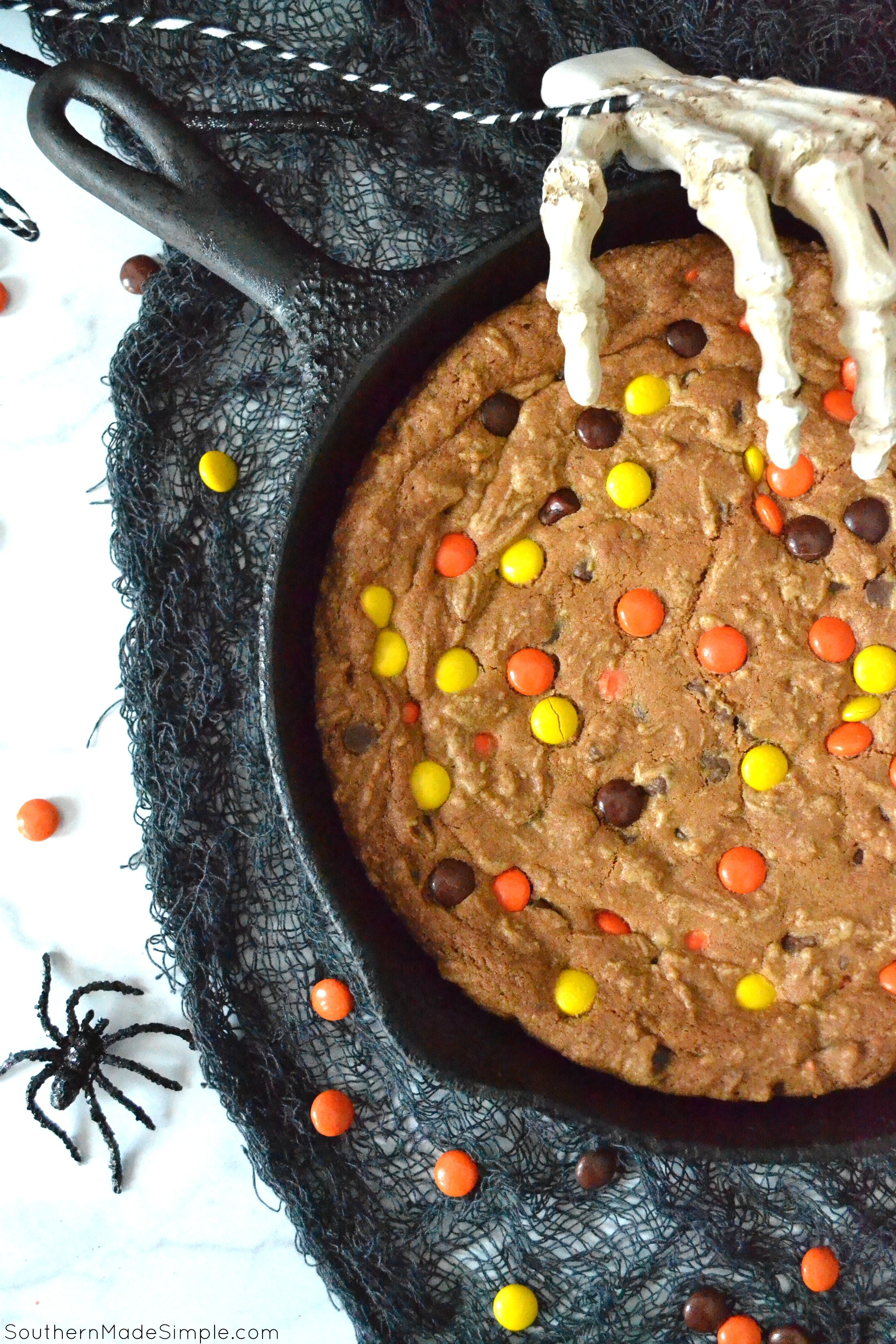 This Halloween Deep Dish Skillet Cookie is filled with chocolate chips, reese's pieces and is baked to perfection in a cast iron skillet! The only thing scary about this cookie is how GOOD it is! #halloweendessert #reesespieces #halloween